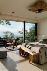 a-cozy-eclectic-bedroom-with-an-upholstered-bed-a-wooden-bench-and-a-fan-rattan-lamps-and-a-rocker-chair-on-the-balcony