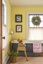 a-farmhouse-bathroom-with-yellow-walls-a-grye-bathtub-printed-textiles-some-artworks-and-greenery-and-foliage