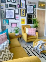 a-fun-and-bright-living-room-with-a-yellow-sofa-and-chairs-printed-pillows-and-blankets-a-bold-gallery-wall-and-a-marquee-light