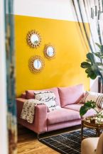 a-fun-living-room-with-a-yellow-accent-wall-a-pink-sofa-printed-textiles-sunburst-mirrors-and-potted-plants