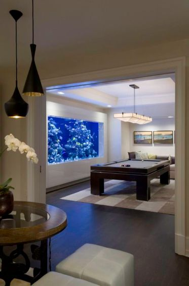 a-game-room-finished-with-a-large-aquarium-that-takes-almost-the-whole-wall-looks-very-relaxing-and-cool