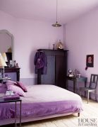 a-lavender-bedroom-with-dark-stained-furniture-a-vintage-table-and-chair-shiny-metallic-touches-and-a-mirror
