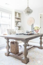 a-light-filled-farmhouse-home-office-with-a-large-wooden-desk-neutral-storage-units-a-crystal-chandelier-and-neutral-blooms