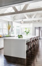 a-light-filled-kitchen-with-whitewashed-wooden-beams-skylights-and-a-large-kitchen-island-plus-wooden-stools