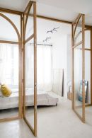 a-light-filled-neutral-bedroom-with-glass-walls-a-bed-a-mirror-and-some-art-is-very-cool-and-feels-very-airy