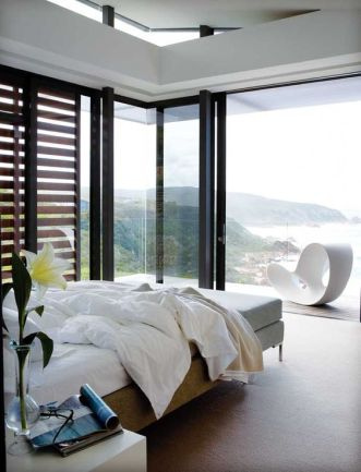 a-lovely-contemporary-bedroom-with-a-bed-a-bench-nightstands-glass-walls-and-a-balcony-plus-amazing-ocean-views