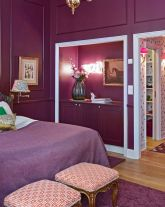 a-luxurious-purple-bedroom-done-with-paneling-a-bed-with-purple-and-white-bedding-refined-stools-and-a-niche-for-books