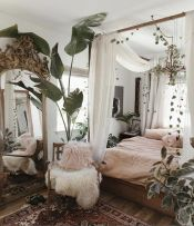 a-messy-boho-spring-bedroom-with-wooden-furniture-pink-bedding-a-boho-rug-and-lots-of-greenery-and-plants