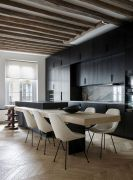 a-minimalist-kitchen-with-black-cabinets-a-marble-backsplash-a-two-part-kitchen-island-and-rough-wooden-beams