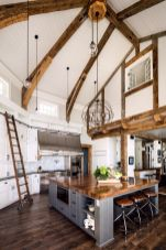 a-modern-farmhouse-kitchen-with-white-cabinetry-a-grey-kitchen-island-wooden-beams-and-countertops-and-pendant-lamps
