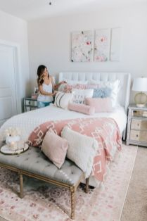 a-modern-feminine-bedroom-with-a-white-upholstered-bed-mirror-nightstands-a-grey-bench-pink-and-white-bedding-and-floral-artworks