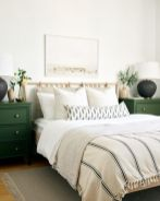 a-modern-spring-bedroom-with-green-nightstands-printed-bedding-a-neutral-artwork-and-greenery