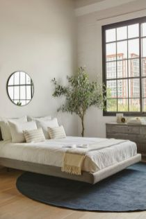 a-modern-zen-bedroom-with-a-grey-floating-bed-a-reclaimed-wooden-dresser-a-statement-plant-neutral-bedding-and-a-round-mirror