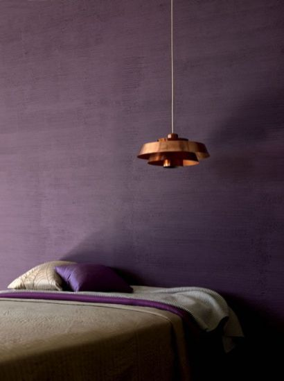 a-moody-bedroom-with-a-textural-purple-wall-some-purple-and-grey-bedding-and-a-copper-pendant-lamp-over-the-bed