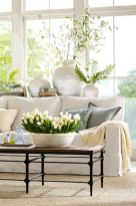 a-neutral-and-pastel-living-room-with-potted-greenery-and-blooms-with-printed-vases-and-a-glazed-wall-is-fresh-and-spring-like
