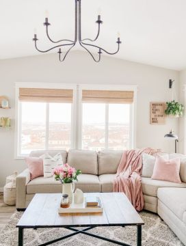 a-neutral-farhouse-livng-room-with-light-pink-linens-potted-greenery-and-blooms-and-a-printed-rug-is-welcoming