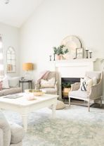 a-neutral-farmhouse-living-room-with-printed-chairs-and-a-printed-rug-potted-greenery-pink-linens-and-mirrors