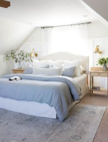 a-neutral-farmhouse-spring-bedroom-with-a-white-bed-wooden-nightstands-blue-and-white-bedding-gold-sconces-and-greenery