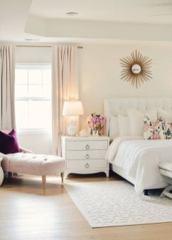 a-neutral-feminine-bedroom-with-a-white-upholstered-bed-white-nightstands-a-blush-couch-and-a-purple-pillow-and-blush-curtains