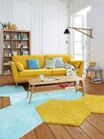 a-pretty-mid-century-modern-living-room-with-a-yellow-sofa-a-geometric-blue-and-yellow-rug-an-open-storage-unit-and-a-wall-sconce