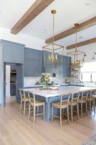 a-refined-blue-kitchen-with-white-surfaces-wooden-beams-wooden-chairs-and-brass-chandeliers-is-stylish-and-chic