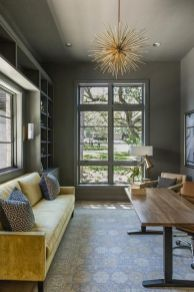 a-refined-home-office-with-grey-walls-built-in-storage-units-a-yellow-sofa-leather-chairs-a-desk-and-gold-touches