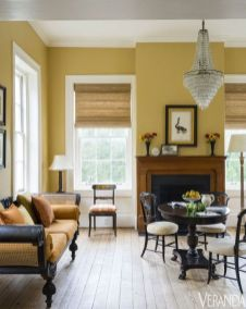 a-refined-vintage-living-room-with-pale-yellow-walls-a-fireplace-dark-wooden-furniture-with-yellow-upholstery-and-a-crystal-chandelier