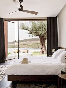 a-relaxed-modern-bedroom-with-dark-wooden-furniture-neutral-bedding-and-a-glass-wall-with-a-door-to-the-terrace-plus-black-curtains