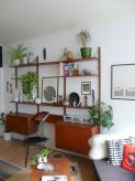a-rich-stained-mid-century-modern-storage-unit-of-shelves-and-cabinets-to-display-stuff-and-features-a-mini-desk