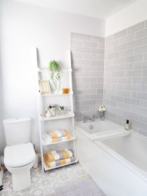 a-serene-bathroom-with-grey-subway-tiles-white-appliances-and-a-shelf-grey-white-and-yellow-towels