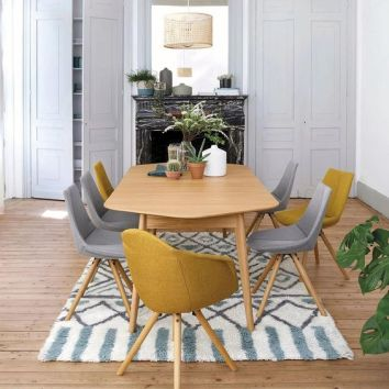 a-small-and-cozy-modern-dining-space-with-grey-storage-units-a-black-marble-fireplace-a-wooden-chair-grey-and-yellow-chairs-and-potted-plants