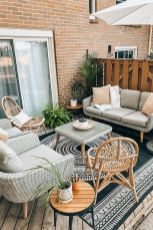 a-small-beach-terrace-with-neutral-wicker-furniture-rattan-chairs-potted-plants-and-a-bold-boho-rug