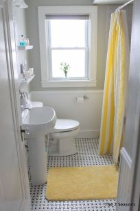 a-small-bright-bathroom-with-grey-walls-and-white-paneling-wihte-appliances-bright-yellow-textiles-is-super-cool