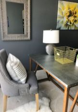 a-small-home-office-nook-with-grey-walls-a-grey-desk-and-a-chair-a-pretty-lamp-with-a-grey-base-and-some-yellow-accessories