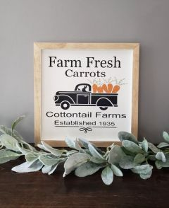 a-small-spring-sign-with-a-truck-carrying-carrots-with-some-letters-and-in-a-simple-wooden-frame