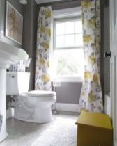 a-small-vintage-bathroom-with-grey-walls-and-a-floor-grey-and-yellow-floral-curtains-white-appliances-is-a-very-chic-space