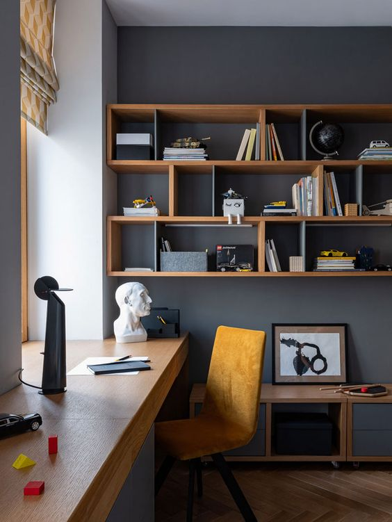 a-stylish-modern-home-office-with-graphite-grey-walls-a-windowsill-desk-an-open-shelving-unit-a-yellow-suede-chair-and-a-cabinet
