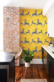 a-stylish-retro-kitchen-with-black-and-white-cabinetry-a-black-kitchen-island-a-brick-pillar-and-yellow-zebra-wallpaper