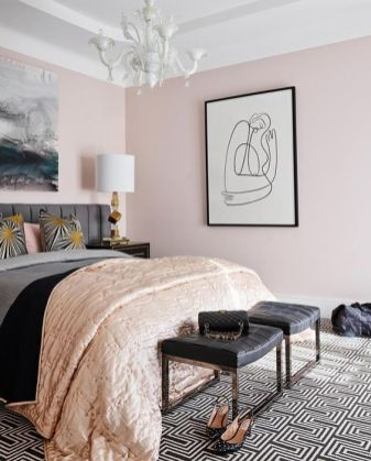 a-super-stylish-feminine-bedroom-with-light-pink-walls-a-grey-bed-black-woven-stools-a-statement-artwork-and-touches-of-gold