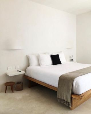 a-very-simple-zen-bedroom-with-a-simple-wooden-bed-a-low-stool-and-floating-nightstands-neutral-bedding-and-wall-lamps