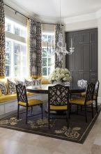 a-vintage-and-refined-dining-room-with-a-bay-window-a-windowsill-seat-a-round-table-black-and-yellow-chairs-a-graphite-grey-storage-unit