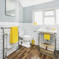 a-vintage-bathroom-with-grey-walls-and-white-subway-tiles-vintage-fixtures-mirrors-and-yellow-accessories-and-touches