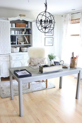 a-vintage-farmhouse-home-office-with-a-large-white-storage-unit-a-neutral-desk-a-sphere-chandelier-and-a-fluffy-fur-chair