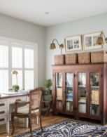 a-vintage-farmhouse-home-office-with-a-white-desk-a-rattan-chair-and-a-storage-unit-baskets-and-brass-scones