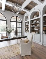 a-vintage-farmhouse-home-office-with-white-walls-and-storage-units-a-sphere-chandelier-a-modern-desk-and-an-upholstered-chair