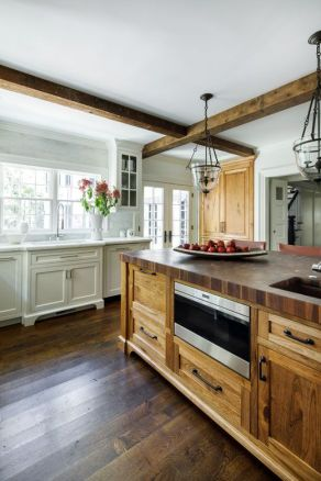 a-vintage-kitchen-with-neutral-cabinets-a-stained-wooden-kitchen-island-and-wooden-beams-that-match-and-look-cozy