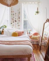 a-warm-spring-bedroom-with-a-wooden-bed-a-pink-chair-pink-and-yellow-pillows-faux-blooms-attached-to-the-wall