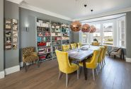 a-welcoming-dining-room-with-a-bay-window-grey-walls-a-wooden-table-yellow-chairs-copper-pendant-lamps-and-a-wall-storage-unit