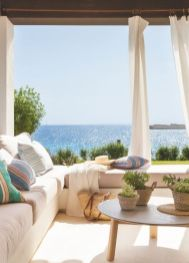 a-welcoming-seaside-patio-with-a-corner-bench-potted-greenery-baskets-colorful-pillows-and-a-fantastic-view