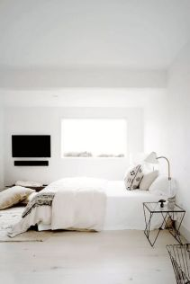 a-welcoming-zen-bedroom-with-a-bed-lightweight-glass-nightstands-sconces-pillows-and-blankets